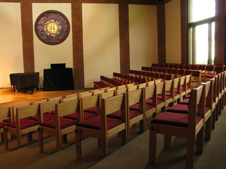 Rogers Memorial Chapel interior view- rows of chairs facing a stained glass window